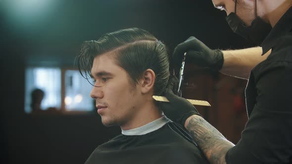 Cover Image for A Young Man Having a Haircut in Barbershop By the Tattooed Barber in Gloves