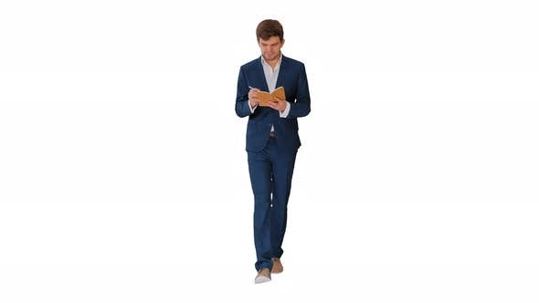Thumbnail for Young Businessman Thinking and Writing Notes in His Notebook While Walking on White Background