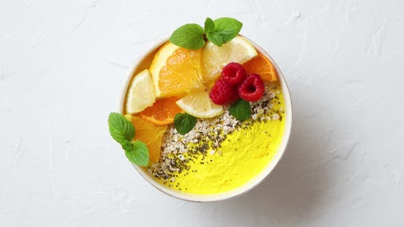 Cover Image for Tasty Orange Fresh Smoothie or Yogurt Served in Bowl. With Raspberries, Orange Slices, Chia Seeds