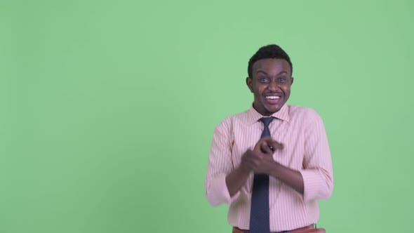 Thumbnail for Happy Young African Businessman Looking Excited While Pointing Up
