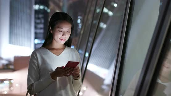 Thumbnail for Woman use of mobile phone at business district at night