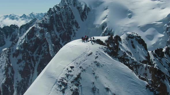 Alpinists on Top of Snow-Capped Mountain in Sunny Day. Aerial View