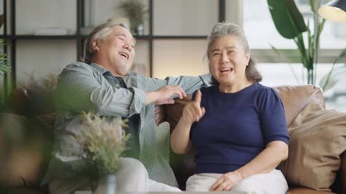 senior asian retired couple enjoy talking conversation together on sofa with happiness