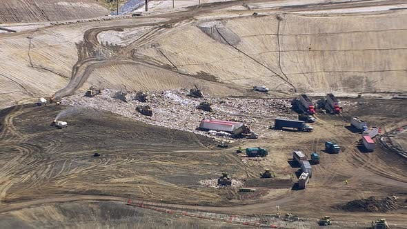 Thumbnail for Aerial shot of trucks and tractors working in landfill