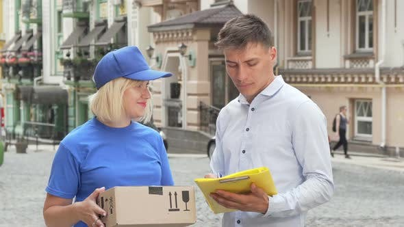Thumbnail for Handsome Young Man Signing Papers Receiving a Package From Delivery Woman