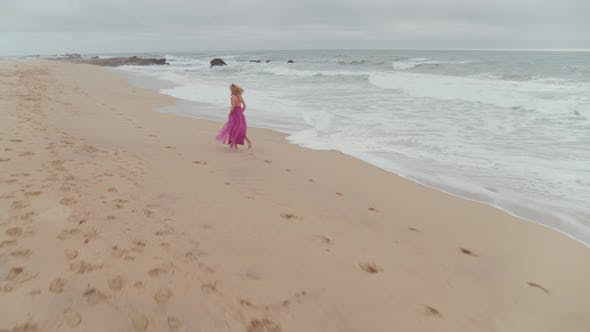 Woman In A Dress Wandering On The Beach