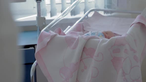 Newborn baby girl sleeping during her first days in maternity hospital