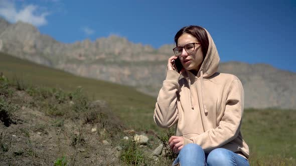 Thumbnail for A Young Woman in a Sweatshirt Sits in the Mountains and Speaks on the Phone. The Girl Travels in the