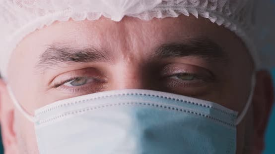 Thumbnail for Extreme Close Up Portrait of Doctor Wearing Protective Medical Mask and Disposable Cap