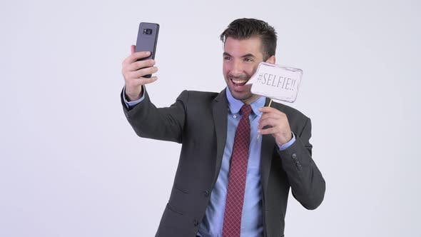 Thumbnail for Young Happy Hispanic Businessman Taking Selfie with Paper Sign