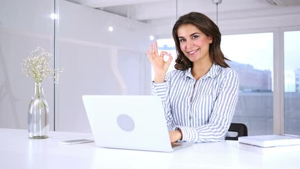 Thumbnail for Satisfied Young Hispanic Woman Gesturing  Okay Sign at Work