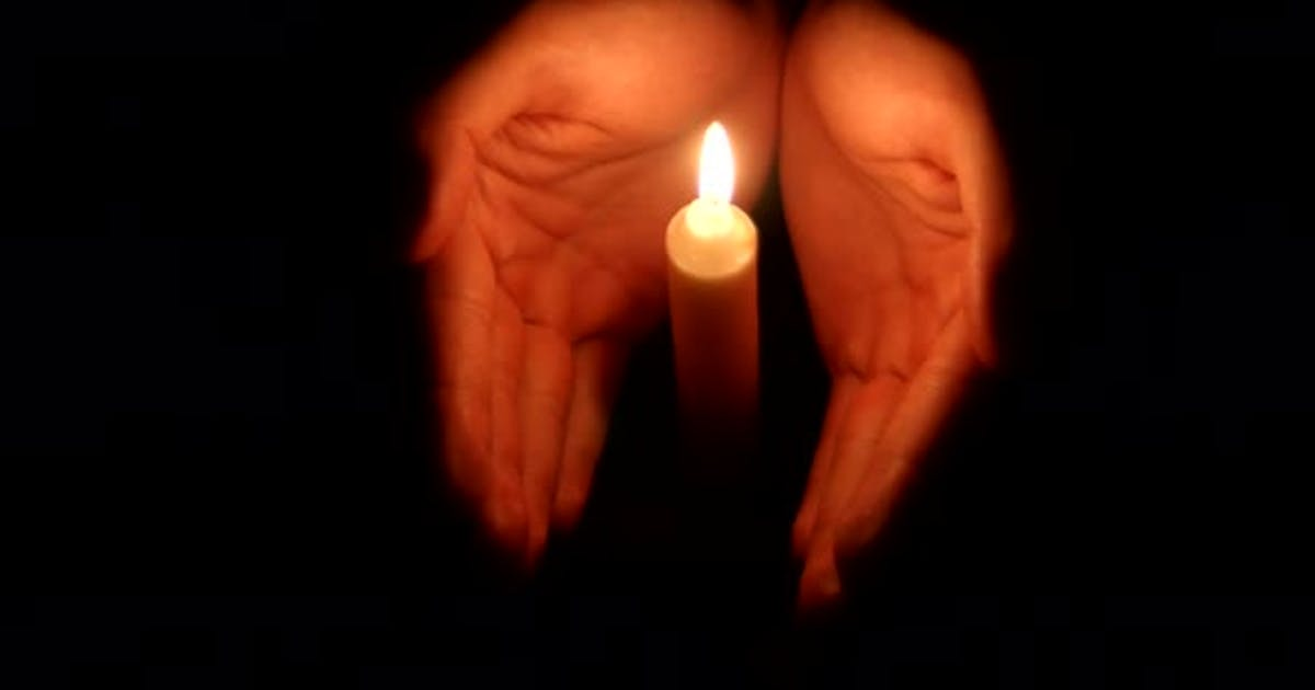 Hands Holding a Burning Candle in Dark 003