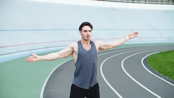Thumbnail for Male Runner Warming Up Before Running Workout on Track. Fit Man Stretching Hands