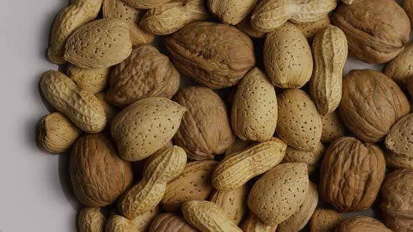 Cinematic, rotating shot of a variety of nuts on a white surface - NUTS MIXED