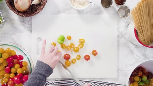 Thumbnail for Flat lay. Step by step. Cutting vegetables on a white cutting board to make a one-pot pasta recipe.