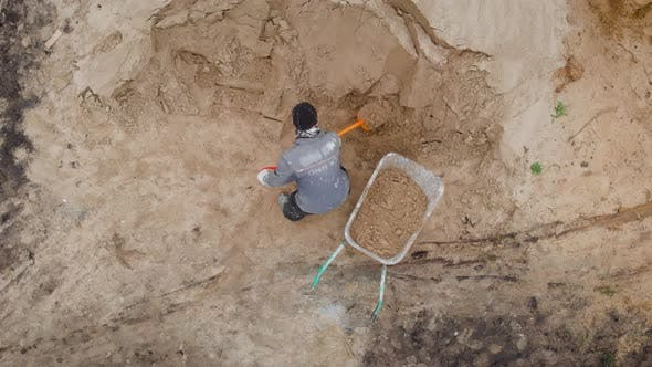 Thumbnail for An Aerial View. A Worker in Special Clothes Digs a Sand Heap. A Light Shovel in Action.