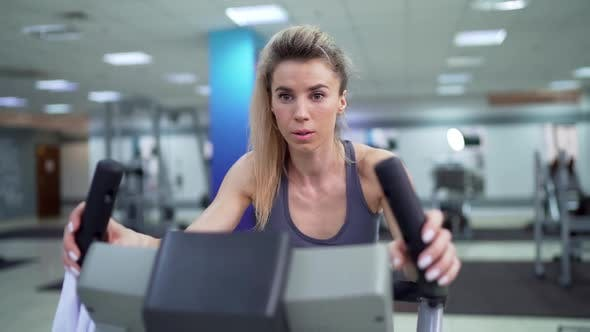 Young woman on bike at gym exercising