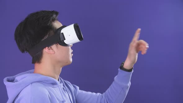 Thumbnail for Joyful Japanese Youngster Playing Videogame in Virtual Reality Helmet on Dark Blue Background.