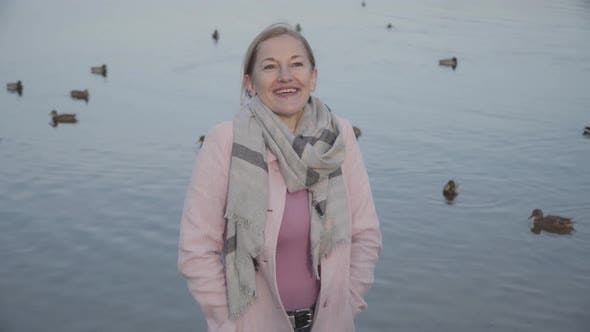 Thumbnail for Middle Shot of Smiling Caucasian Lady in Pink Coat at the Background of Ducks Flying and Swimming on