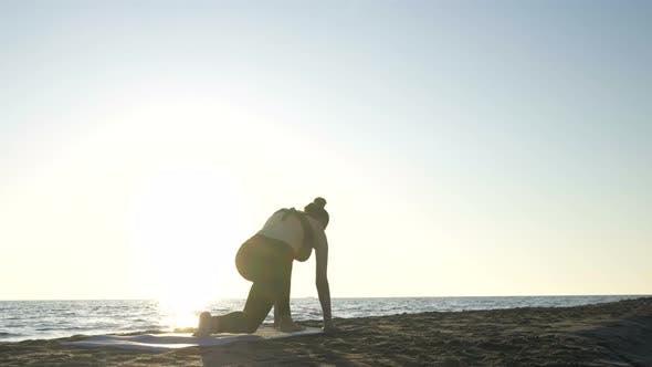 Young Caucasian Woman Practicing Yoga on the Beach Near Calm Sea.