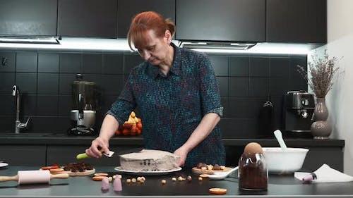 Konditorin kocht Schokoladen-Sahnetorte in der modernen Küche