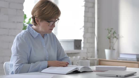 Cover Image for Old Woman Reading Book in Office