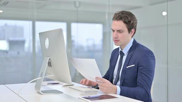 Thumbnail for Serious Young Businessman Doing Paperwork in Modern Office