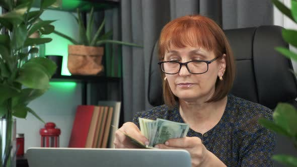 Focused businesswoman is holding bundle of banknotes in hands and counting money