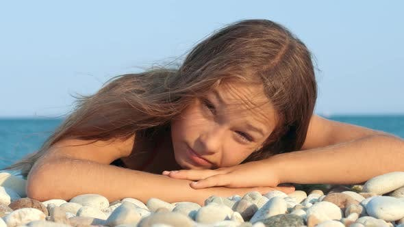 Thumbnail for Young Girl Smiling on Sea Beach. Portrait of Smiling Girl Lying on Pebble Beach