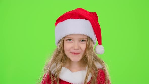 Thumbnail for Child Girl in a Beautiful Suit and a Red New Year's Cap Smiles. Green Screen