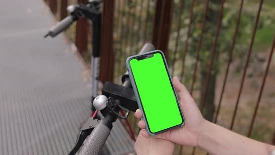 Thumbnail for Woman is unlocking rental bike using a mobile phone iPhone 11 with pre-keyed green screen.