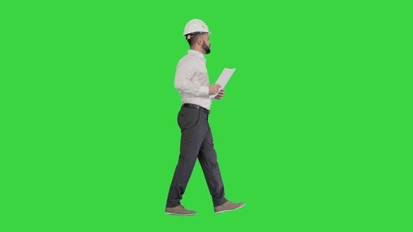 Thumbnail for Männlicher Bauunternehmer Ingenieur mit Schutzhelm Gehen, Objekt betrachten und in Papiere, Dokumente