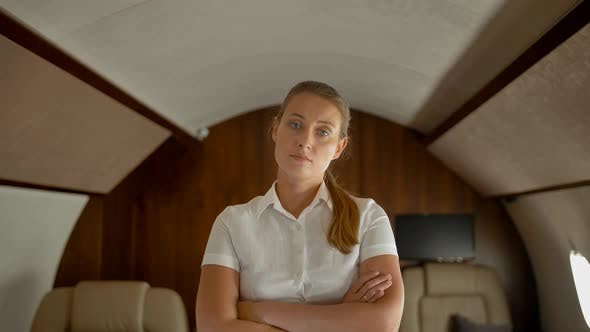 Thumbnail for Confident Businesswoman Inside of Private Jet Standing, Seriously Looking at Camera