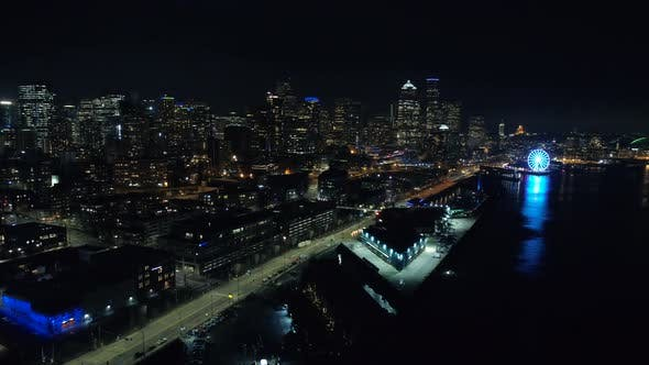 Helicopter View Of Seattle Waterfront At Night In Vibrant Lighting