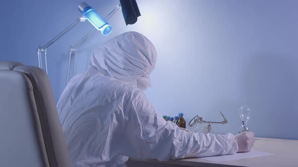 Thumbnail for Back Side View of Lab Assistant in Protective Suit Looking at Cotton Swab Under Magnifying Glass and