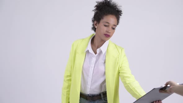 Cover Image for Young Stressed African Businesswoman Showing Clipboard and Giving Thumbs Down
