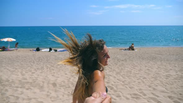 Thumbnail for Follow Me Shot of Young Woman Pull Her Boyfriend To the Sea Shore. Beautiful Girl Holding Male Hand