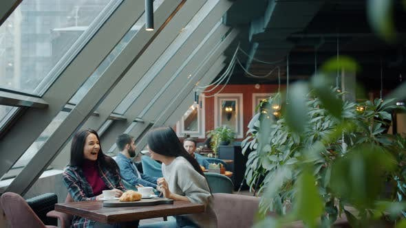 Happy Girls Friends Talking and Laughing Sitting at Table in Cafe Together Enjoying Conversation