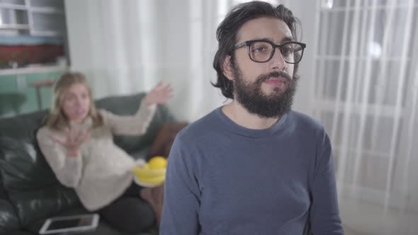 Thumbnail for Exhausted Caucasian Man in Eyeglasses Making Faces As His Pregnant Wife Yelling at Him
