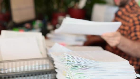 Thumbnail for A Man Parses Papers in the Office and Stacks Them in a Pile. Focus on a Stack of Papers.