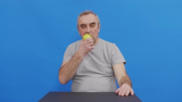 Portrait of Senior Male Pensioner at Eating an Apple. Beautiful Old Male with Gray Hair Poses for
