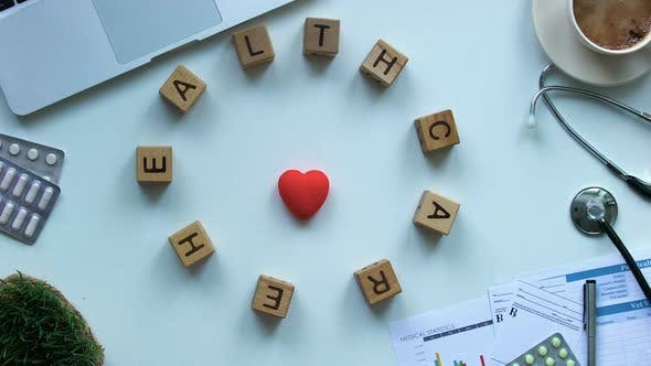 Thumbnail for Healthcare on Wooden Cubes Moving Around Toy Heart on Doctors Table, Stop Motion
