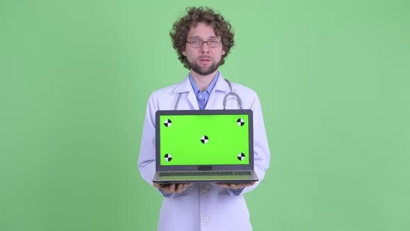 Thumbnail for Happy Young Bearded Man Doctor Talking While Showing Laptop
