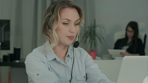 Cover Image for Call Operator with Headset Using Laptop at the Desk in Work