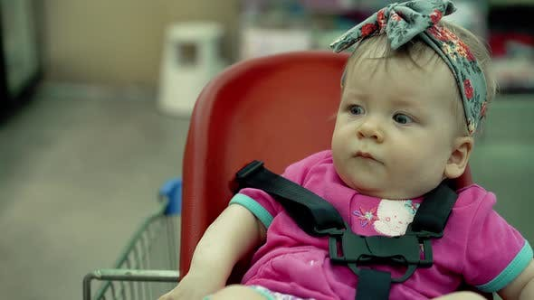 Child Sits in a Specially Equipped Chair in a Trolley