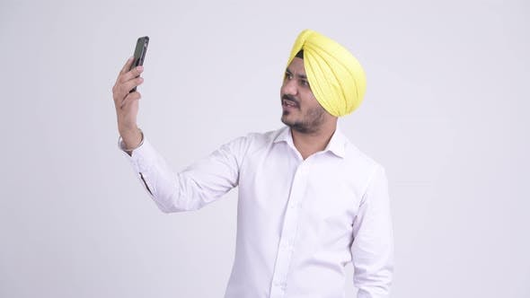 Cover Image for Happy Bearded Indian Sikh Businessman Video Calling with Phone