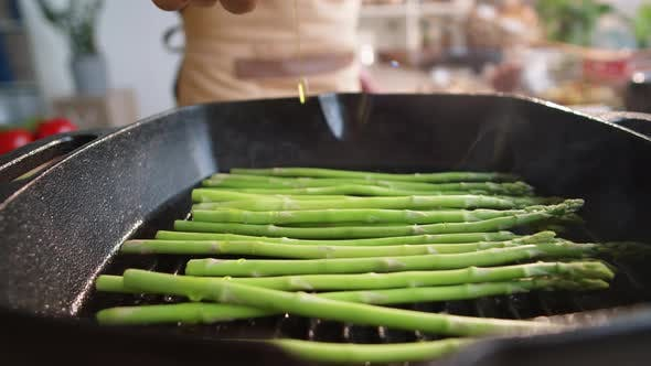 Thumbnail for Cook Pouring Olive Oil over Asparagus on Pan
