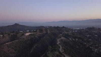 AERIAL Over Hollywood Hills at Sunrise with View on Hills and the Valley and Power Lines in Los