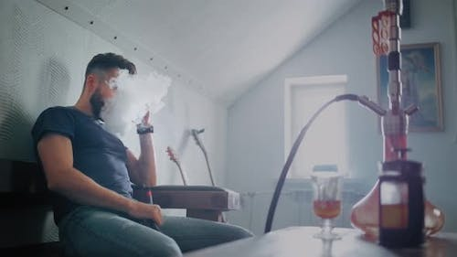 The Guy Smokes a Hookah Indoors and Exhales Smoke