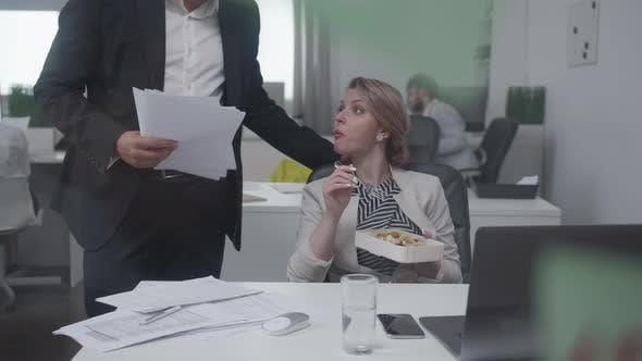 Thumbnail for Woman Eat at the Office, Man Gives Her Documents